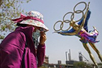 In this May 2, 2021, file photo, a woman adjusts her face mask as she walks by a statue featuring the Beijing Winter Olympics figure skating on display at the Shougang Park in Beijing. (AP Photo/Andy Wong)