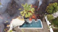 Hot lava reaches a swimming pool after an eruption of a volcano on the island of La Palma in the Canaries, Spain, on Sept. 20, 2021. (Europa Press via AP)