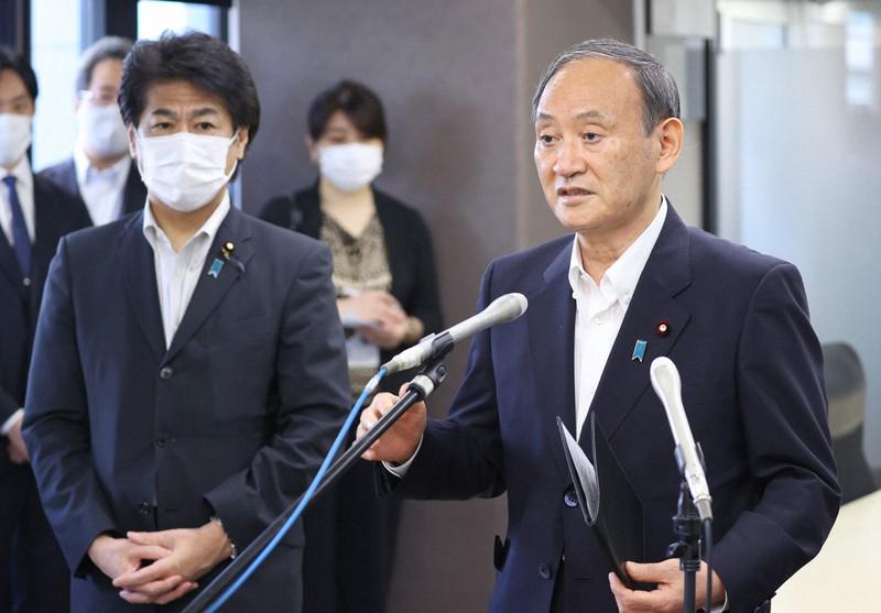 ファストドクターを視察後、報道陣の取材に応じる菅義偉首相。左は田村憲久厚労相=東京都新宿区で2021年9月15日(代表撮影)