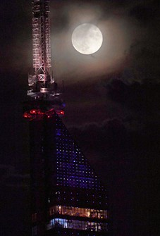 A full harvest moon is seen through wisps of cloud from Fukuoka's Nishi Ward on Sept. 21, 2021. Fukuoka Tower is seen in the foreground. (Mainichi/Yoshiyuki Hirakawa)