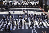 Visitors wearing protective masks to help curb the spread of the coronavirus walk at pedestrian crossings on Sept. 20, 2021 in Tokyo. (AP Photo/Eugene Hoshiko)