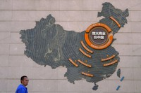 A custodian stands near a map showing Evergrande development projects in China on a wall in an Evergrande city plaza in Beijing, on Sept. 21, 2021.  (AP Photo/Andy Wong)