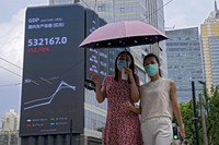 In this Aug. 24, 2021, file photo, women wearing face masks to help curb the spread of the coronavirus walk by an electronic billboard showing China's Gross Domestic Product (GDP) index on a commercial office building in Shanghai, China. (AP Photo/Andy Wong)