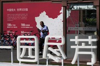 A security guard walks by a map showing Evergrande development projects in China at an Evergrande new housing development in Beijing, on Sept. 22, 2021. (AP Photo/Andy Wong)