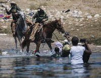 U.S. Customs and Border Protection mounted officers attempt to contain migrants as they cross the Rio Grande from Ciudad Acuna, Mexico, into Del Rio, Texas, on Sept. 19, 2021. (AP Photo/Felix Marquez)