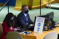 United Nations employees work at a desk with a sign informing the coronavirus protocols during the 76th Session of the United Nations General Assembly, on Sept. 21, 2021 at U.N. headquarters. (AP Photo/Mary Altaffer, Pool)