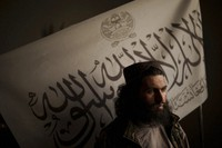 Taliban district police chief Shirullah Badri stands in front of a Taliban flag during an interview at his office in Kabul, Afghanistan, on Sept. 20, 2021. (AP Photo/Felipe Dana)