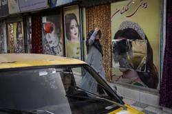 広告の女性の顔が覆い隠された美容院の前を通り過ぎる女性=アフガニスタンの首都カブールで2021年9月12日、AP