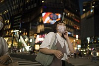 A woman wearing a mask crosses an intersection in the Ginza shopping district in Tokyo, on Sept. 23, 2021. (AP Photo/Hiro Komae)