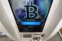 In this Feb. 9, 2021, file photo, the Bitcoin logo appears on the display screen of a cryptocurrency ATM at the Smoker's Choice store in Salem, N.H. (AP Photo/Charles Krupa)