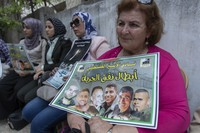 """A Palestinian woman carries a poster with pictures of the six Palestinian prisoners who escaped from an Israeli jail that says """"heroes of the freedom tunnel,"""" during a protest in the West Bank city of Ramallah, on Sept. 14, 2021. (AP Photo/Nasser Nasser)"""