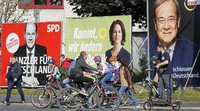 People walk and drive past election posters of the three chancellor candidates, from right, Armin Laschet, Christian Democratic Union (CDU), Annalena Baerbock, German Green party (Die Gruenen) and Olaf Scholz, Social Democratic Party (SPD), at a street in Gelsenkirchen, Germany, on Sept. 23, 2021. (AP Photo/Martin Meissner)
