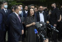 Meng Wanzhou, chief financial officer of Huawei, reads a statement outside British Columbia Supreme Court in Vancouver, Canada, on Sept. 24, 2021. (Darryl Dyck/The Canadian Press via AP)