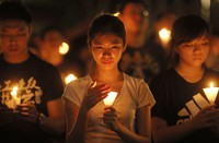 In this June 4, 2015 file photo, people attend a candlelight vigil at Victoria Park in Hong Kong. (AP Photo/Vincent Yu)