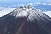 This Sept. 7, 2021 photo taken from a Mainichi Shimbun helicopter shows snow dusting the summit of Mount Fuji. The date was initially announced as the peak's first snowcap of the season, but this was rescinded on Sept. 20 due to high temperatures. (Mainichi/Hiroshi Maruyama)
