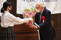Sen Genshitsu, former grand master of the Urasenke tea school, is seen receiving flowers from a high school student after giving a lecture in Kyoto's Shimogyo Ward on Aug. 3, 2021. (Mainichi/Kazuki Yamazaki)
