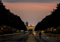A man rides his bike towards the Brandenburg Gate in Berlin, Germany, before sunrise on Sept.27, 2021, a day after the German elections. (AP Photo/Michael Probst)