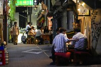 People gather at bars in an alley in Tokyo that are serving alcohol on Sept. 22, 2021, despite the capital government's request for businesses not to serve alcohol under the state of emergency. (AP Photo/Kiichiro Sato)