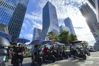 Men on electric bikes wait for riders near the Evergrande headquarters, center, in Shenzhen, China, on Sept. 24, 2021. (AP Photo/Ng Han Guan)