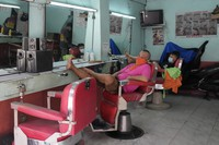 In this Sept. 16, 2021 file photo, barbers wait for customers after reopening their shop following easing of COVID restrictions in Quezon city, Philippines. (AP Photo/Aaron Favila)