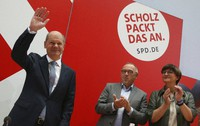German Social Democratic Party, SPD, party leaders Saskia Esken, right, and Norbert Walter-Borjans, center, applaud to the party's candidate for chancellery Olaf Scholz as he arrives at the meeting of the SPD Federal Executive Committee in Berlin, Germany, on Sept. 27, 2021. (Wolfgang Kumm/dpa via AP)