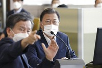In this photo provided by the South Korea Presidential Blue House, South Korean President Moon Jae-in, center, listens to official at a test center of the Agency for Defense Development in South Korea, on Sept. 15, 2021. (South Korea Presidential Blue House/Yonhap via AP)