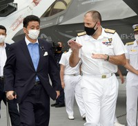 In this Sept. 6, 2021 photo, Commodore Steve Moorhouse, right, commander of the strike group centered on Britain's aircraft carrier the Queen Elizabeth, speaks to Japan Defense Minister Nobuo Kishi on the deck of British Royal Navy's HMS Queen Elizabeth aircraft carrier, at the U.S. naval base in Yokosuka, Kanagawa Prefecture. (Pool photo)