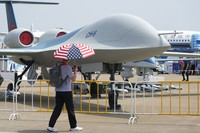 A man carrying an umbrella with the United States flag colors walks past the CH-6 drone during the 13th China International Aviation and Aerospace Exhibition, also known as Airshow China 2021, on Sept. 28, 2021, in Zhuhai in southern China's Guangdong province. (AP Photo/Ng Han Guan)
