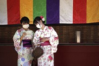 Visitors in yukatas or Japanese traditional summer kimonos wear protective masks to help curb the spread of the coronavirus as they draw a fortune-telling paper strip at the Sensoji Temple in the Asakusa district, on Sept. 20, 2021 in Tokyo. (AP Photo/Eugene Hoshiko)