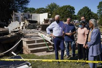 In this Sept. 7, 2021, file photo President Joe Biden tours a neighborhood impacted by Hurricane Ida in Manville, N.J. Rep. Bonnie Watson Coleman, D-N.J., looks on at right. (AP Photo/Evan Vucci)