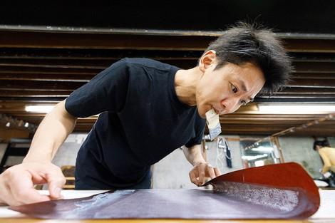 Yuichi Hirose, fourth-generation head of Hirose Dyeworks, is seen applying paste to silk fabric at the Edo Komon workshop in Tokyo's Shinjuku Ward on July 8, 2020. (Mainichi/Kota Yoshida)