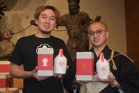 Naoki Itatoko, left, head of Yucho Shuzo Co.'s Yamato Distillery, and Yuou Ueda, deputy chief priest of Abe-Monjuin Temple, are seen holding Kikka Gin Seimei craft gin products at Abe-Monjuin Temple in Sakurai, Nara Prefecture, on Oct. 8, 2021. (Mainichi/Akiko Hirose)