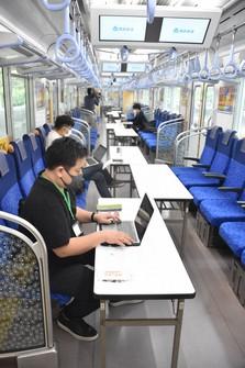 People are seen working on desks set up inside parked train cars in Tokorozawa, Saitama Prefecture. (Mainichi/Takashi Seido)