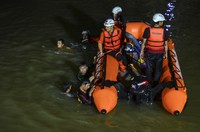 Rescuers search for victims of drowning in a river in Ciamis, West Java, Indonesia, on Oct. 15, 2021. (AP Photo/Yopi Andrias)
