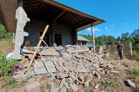 A man stands near his house damaged by an earthquake in Karangasem on the island of Bali, Indonesia, on Oct. 16, 2021. (AP Photo/Andi Husein)