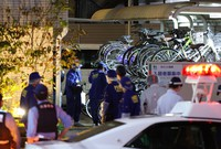 Police officers investigate the scene where a woman was fatally stabbed in Amagasaki, Hyogo Prefecture on Oct. 15, 2021. (Mainichi/Kenji Ikai)