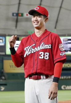 Koki Ugusa of the Hiroshima Carp strikes a victory celebration pose after the team's win over the Yomiuri Giants in their Central League at Tokyo Dome on Oct. 16, 2021. (Kyodo)