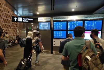 カタールのドーハ国際空港で乗り継ぎ便の確認をする利用客ら=2021年3月26日、平野光芳撮影