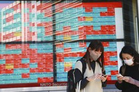 People stand by an electronic stock board of a securities firm in Tokyo, on Oct. 18, 2021. (AP Photo/Koji Sasahara)