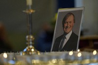 Candles are lit next to a portrait of British Lawmaker David Amess during a vigil for him at St Michaels Church, in Leigh-on-Sea, England Sunday, Oct. 17, 2021. (AP Photo/Alastair Grant)