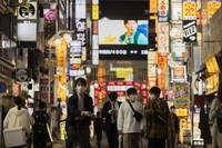 In this Oct. 1, 2021, file photo, people walk through the famed Kabukicho entertainment district of Tokyo on the first night of the government's lifting of a coronavirus state of emergency. (AP Photo/Hiro Komae)