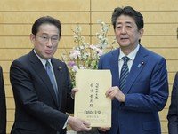 Then Prime Minister Shinzo Abe, right, accepts from then Liberal Democratic Party (LDP) policy chief Fumio Kishida a request for economic measures from the LDP's economic growth headquarters and coronavirus-related measures headquarters at the prime minister's office on March 31, 2020. (Mainichi/Masahiro Kawata)
