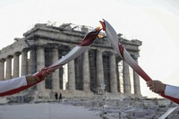 Greek torch bearer Ioannis Melissanidis, left, Olympic gold medalist in gymnastics, passes the flame to world cycling champion Christos Volikakis in front of the ancient Parthenon temple atop of the Acropolis Hill in Athens, on Oct. 19, 2021. (AP Photo/Petros Giannakouris)