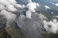 This photo taken from a Mainichi Shimbun helicopter shows a plume of smoke rising from the Nakadake crater of Mount Aso in the city of Aso, Kumamoto Prefecture, on Oct. 20, 2021. The mountain slope is covered with gray volcanic ash. (Mainichi/Takashi Kamiiriki)