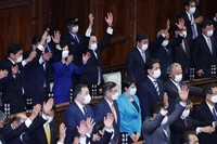 """Japanese Prime Minister Fumio Kishida, center in the back row, and other lawmakers raise their hands in a customary """"banzai,"""" after the dissolution of the lower house was announced at the Diet in Tokyo on Oct. 14, 2021. (Mainichi/Kota Yoshida)"""