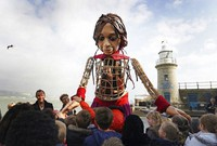 Little Amal, a 3.5-metre-tall puppet of a nine-year-old Syrian girl, is greeted by children from the St. Mary's Primary Academy as she arrives in Folkestone, Kent, on Oct. 19, 2021 as part of the Handspring Puppet Company's 'The Walk'. (Gareth Fuller/PA via AP)