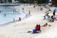 In this Aug. 24, 2021, file photo people sit on Waikiki Beach in Honolulu. Hawaii's COVID-19 case counts and hospitalizations have declined to the point where the islands are ready to welcome travelers once again, the governor said on Oct. 19. (AP Photo/Caleb Jones)