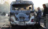 In this photo released by the Syrian official news agency SANA, Syrian security officers gather around a burned bus at the site of a deadly explosion, in Damascus, Syria, on Oct. 20, 2021. (SANA via AP)