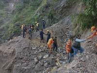 This photograph provided by India's National Disaster Response Force (NDRF) shows NDRF personnel rescuing civilians stranded following heavy rains at Chhara village near Nainital, Uttarakhand, on Oct. 20, 2021. ( National Disaster Response Force via AP)
