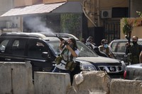In this Oct. 14, 2021, file photo, supporters of a Shiite group allied with Hezbollah fire weapons during armed clashes that erupted during a protest in the southern Beirut suburb of Dahiyeh, Lebanon. (AP Photo/Hassan Ammar)